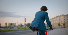 Back View Of Businessman Commuter With Electric Bicycle Traveling To Work In City.