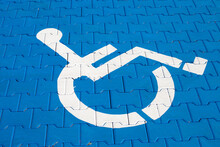 Handicap Parking Sign On A Blue Stone Road