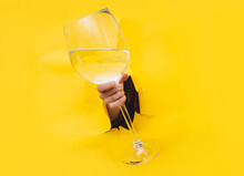A Right Woman's Hand Emerges Through A Torn Hole In Light Yellow Paper With A Large Glass With Vermouth, Water Or Vodka. The Concept Of Alcoholism, Drunkenness And Hangover. Copy Space.
