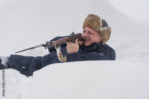 Man and soviet Mosin rifle with a bayonet in a snowy trench in winter Fototapet