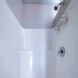 Square frame Shower area with a knob and rack under the shower head.