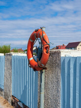 Vertical Shot Of A Lifebuoy Attached To A Metal Pipe