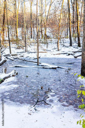 Sugarland Run Stream Valley Trail with vertical view of landscape creek river water covered in frozen snow ice in Herndon, Northern Virginia Fairfax county in winter