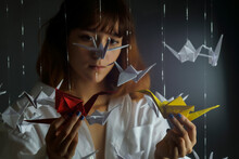 Portrait Of A Young Beautiful Girl With Origami Cranes In A Low Key