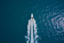 Speedboat Wave Speed Water. Speed Boat Faster Movement On The Water Top View. Speedboat Movement On The Water. Large White Boat Driving On Dark Water. Speedboat On Blue Water Aerial View.