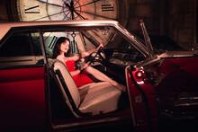 Fashion Model In Red Dress In A Retro Car Invites You To Come In