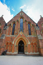 Low Angle Of An Old Red Church Entrance On A Sunny Day