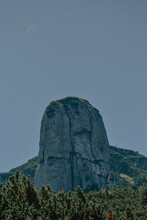 Vertical Shot Of A Volcanic Plug Surrounded By Forest Trees Below It