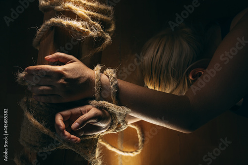 Murais de parede Blond woman tied to the wooden beam with shabby rope, lying on the floor