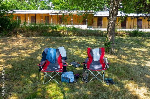 Photo Folding beach chairs in the shade of a tree