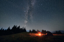 Night Camping Under Amazing Starry Sky And Milky Way. Wide Angle View On Landscape In The Mountains. Two Tents And Campfire, Wall Of Spruces On Background. Concept Of Travelling And Astrophotography