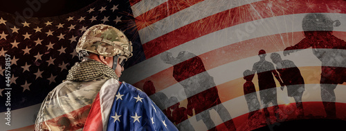 Fotografiet US Soldier in combat uniforms holding the national flag across the shoulder, Dou