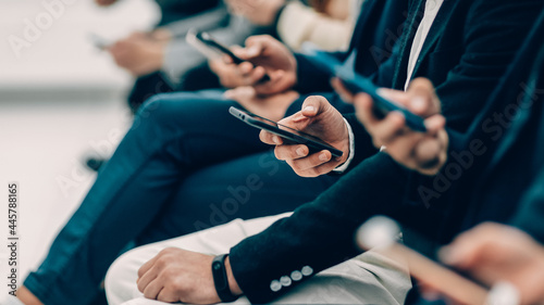 Fotografie, Obraz group of diverse young people with smartphones sitting in a row
