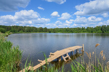 Summer Landscape With A Forest Lake Surrounded By Trees And A Blue Sky With Cumulus White Clouds Floating Peacefully On It. Wooden Walkways For Fishing And Swimming Attract Attention. Russia, Ural