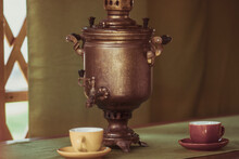 Russian Copper Samovar And Tea Cups On The Table In The Gazebo