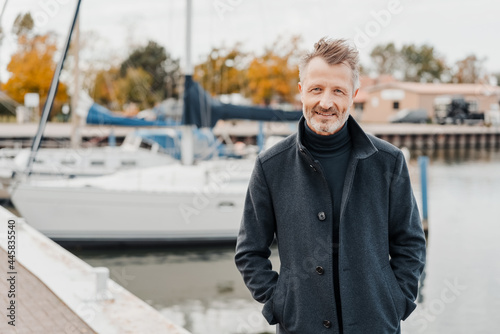 Fototapeta Attractive tousled man standing smiling on a marina jetty