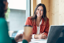 Smiling Young Business Woman Listening Her Partner On Coworking Space.
