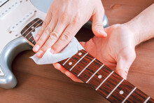 Guitar Master Polishing Fretboard Of Electric Guitar With Cloth
