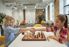 Respect. Adorable Little Friends, Caucasian Boy And Girl Shaking Hands After Match, Playing Chess, Sitting Together At The Table In School