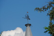 Metal Shooter Weather Vane On An Old House