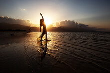 Beautiful Woman Dancing By The Sea At Sunset