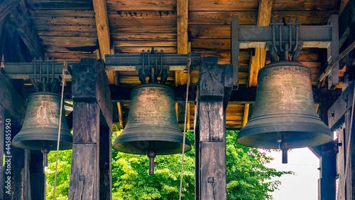 Fotografia, Obraz Three bells hanging in the belfry next to a Gothic church in the village of Miłoradz, Poland