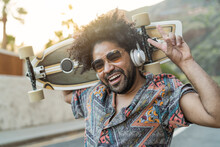 Happy Afro Skater Having Fun Listening To Music With Headphones During Summer Time - Youth People Lifestyle Concept