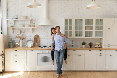 Portrait of affectionate young wife sitting on kitchen counter hug smiling husband from behind at modern renovated interior. Loving young couple homeowners look at camera glad of buying new furniture