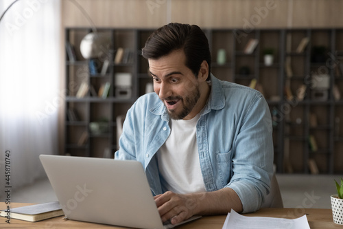 Fotografiet Surprised young male manager worker looking at laptop screen, feeling excited of getting email with amazing news, getting dream job offer or promotion notification, celebrating salary increase