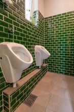 Blick In Ein Außergewöhnliches Gäste-WC. Mit Zwei Urinalen . Besonders Auffällig Sind Die Kleinen Grünen Fliesen