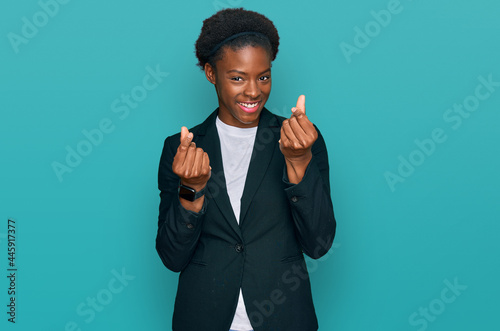 Fotografiet Young african american girl wearing business clothes doing money gesture with ha