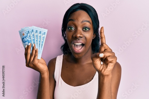 Obraz na plátne Young african american woman holding thai baht banknotes smiling with an idea or