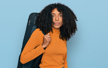 Young African American Girl Wearing Guitar Case Thinking Attitude And Sober Expression Looking Self Confident