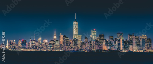 Fotografia New York City Manhattan downtown skyline at dusk with skyscrapers illuminated over Hudson River panorama