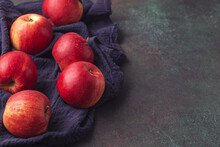 Ripe Apples On Blue Napkin On Dark Background With Copy Space