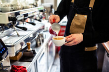 Barista Pouring Milk Into A Cup Of Coffee
