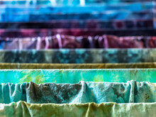 Closeup Of Colorful Hand-dyed Wet Cotton Fabrics Drying On Drier
