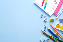 School Stationery, Color Pencils, Paints, Notepad On Blue Table. Back To School Background. Kids Desk Top View.