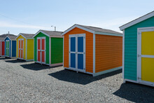 A Row Of Small Colorful Painted Huts Or Sheds Made Of Wood. The Exterior Walls Are Colorful With Double Wooden Doors. The Sky Is Blue In The Background And The Storage Units Are Sitting On Gravel.
