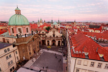 Panoramic View From The Bridge Tower Overlooking A Square In Prague Old Town, Czech, With A Skyline Of Majestic Domes, Red Tiled Roofs And Towering Spires Of Historic Buildings Under Rosy Sunset Sky