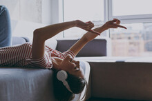 Side Profile View Young Excited Woman 20s In Casual Clothes Headphones Lying On Grey Sofa Listen To Music Modern Remix Dancing Rest On Weekends Indoors Flat At Home. People Lifestyle Leisure Concept