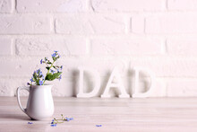 Father's Day Message With Forget-me-not Flowers In A Small Jug On The Background Of A White Brick Wall.