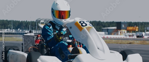 Fototapeta premium Front view of teenager professional racer driving his go kart on a race track. Shot with 2x anamorphic lens