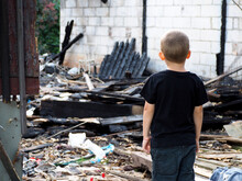 A Little Boy In A Black T-shirt And Pants Stands With His Back Against The Background Of A Burned-out House