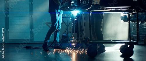 Tela CU Sparks falling on the ground as mechanic welding a go kart car inside garage