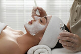 Young woman during face peeling procedure in salon