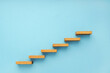 Wooden staircase on blue background. Growth, increasing business, success process concept. Copy space