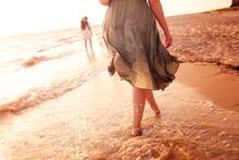 Crop Family Walking In Sea Waves