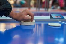 Hand Of Brunette Man Holding Striker On Air Hockey Table In Game Room. Horizontal