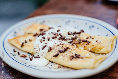 Fototapeta Pancake with cottage cheese, topped with cream and sprinkled with chocolate flak